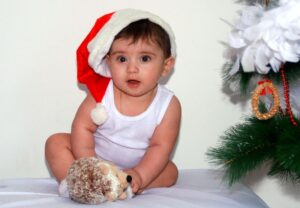 baby wearing a christmast hat and a white sando