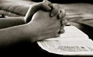 Praying with hands on the Bible, Bible and Thankfulness