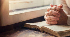 what is prayer- hands praying with bible