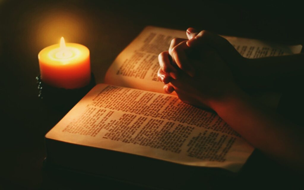 power of prayer-closed hands on the bible with candle