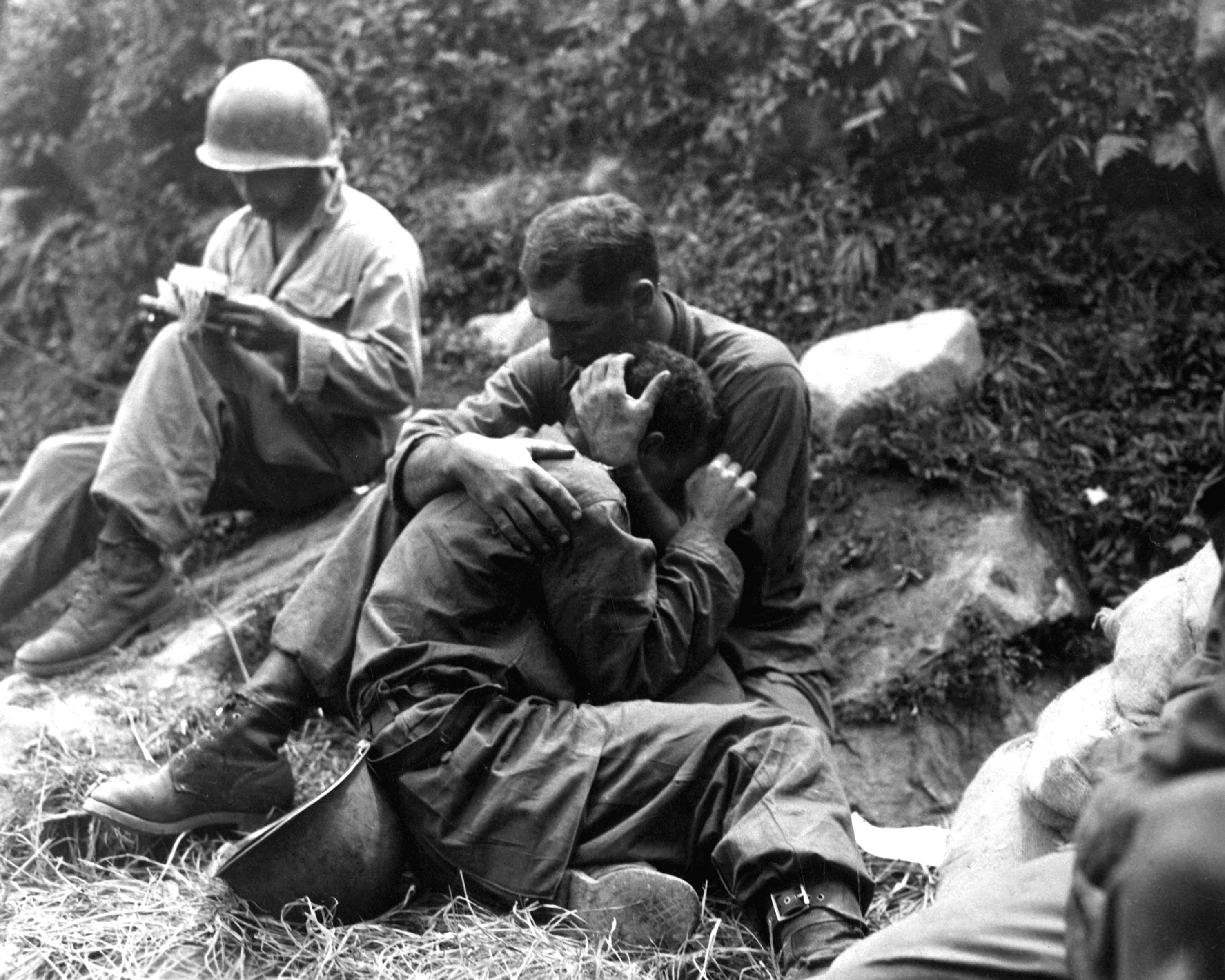 A grief stricken American infantryman whose buddy has been killed in action is comforted by another soldier. In the background a corpsman methodically fills out casualty