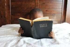 Bible verses about faith - child reading the bible