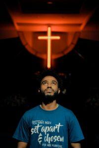 man looking upward with cross behind him