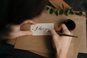 woman writing 'i love you'