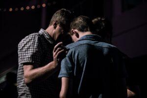man praying for another man