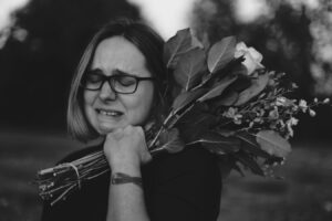 woman with bouquet of flowers crying