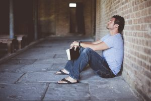 man leaning on wall while holding a black book