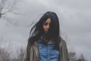 Healing bible verses- a woman looking down while the wind blew her hair
