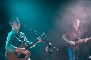 Bible verses about worship - man playing guitar while singing