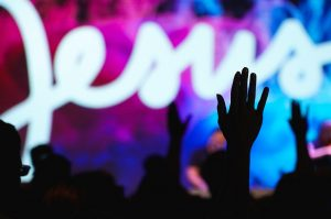 Bible verses about worship - the name Jesus is being projected with hands lifted in worship