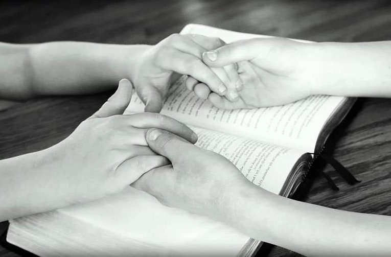 two people joining hands for prayer, Bible verses about prayer