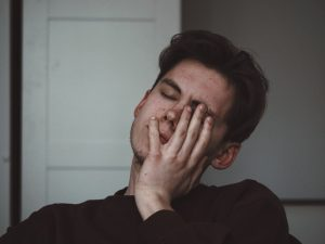man crying with his hand on his face
