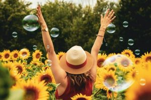 woman surrounded by sunflowers raising her hands