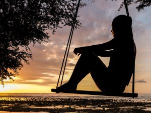 silhouette of a woman on swing