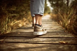 person stands on brown wood pathway